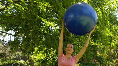 Fit woman lifting up exercise ball in the park Footage