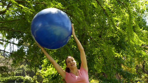 Fit woman lifting up exercise ball in the park Stock Video Footage