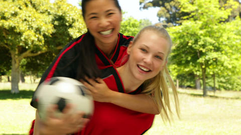 Female football teammates celebrating a win in the park Stock Video Footage