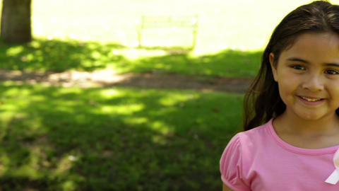 Smiling little girl wearing pink for breast cancer... Stock Video Footage