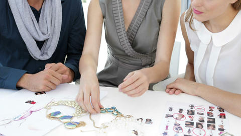 Design team looking at costume jewelry and speaking together Stock Video Footage