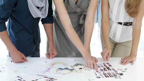 Fashion design team looking at costume jewelry and model... Stock Video Footage