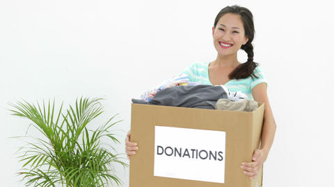 Pretty brunette holding donation box full of clothes Stock Video Footage
