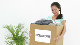 Pretty brunette holding donation box full of clothes Footage