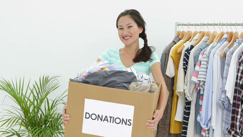 Pretty asian brunette holding donation box full of clothes Stock Video Footage
