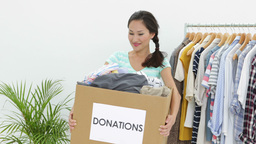 Pretty asian brunette holding donation box full of clothes Footage