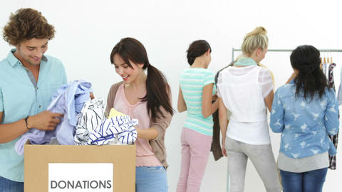 Team of happy workers going through donation box of clothes Stock Video Footage