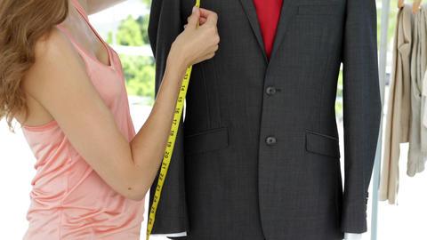 Smiling fashion designer measuring suit on mannequin Stock Video Footage