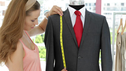 Smiling fashion designer measuring suit on mannequin Footage