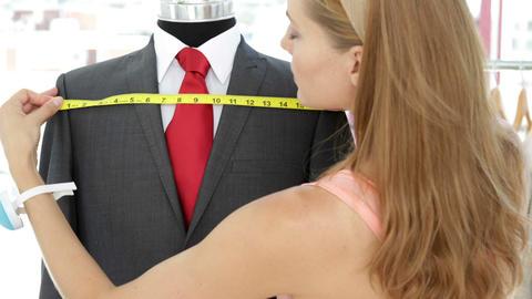 Attractive fashion designer measuring suit on mannequin Footage