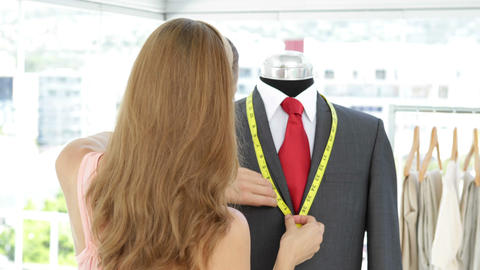 Pretty fashion designer measuring suit lapels on mannequin Stock Video Footage