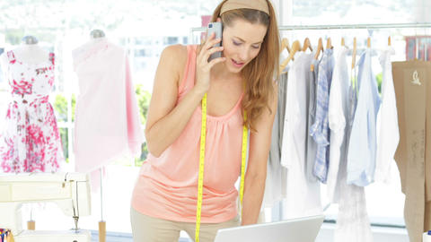 Attractive fashion designer talking on the phone Stock Video Footage