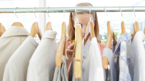 Attractive fashion designer looking at clothes on rail Stock Video Footage