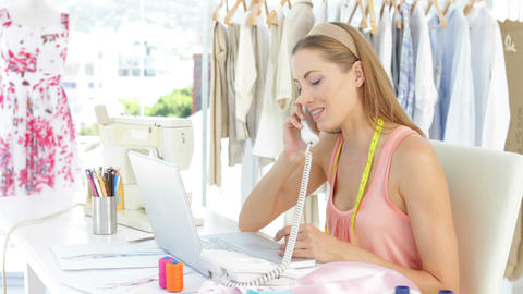Attractive fashion designer working on laptop and answering the phone Footage