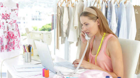 Attractive fashion designer working on laptop and... Stock Video Footage