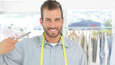 Handsome fashion designer holding a scissors smiling at camera Footage