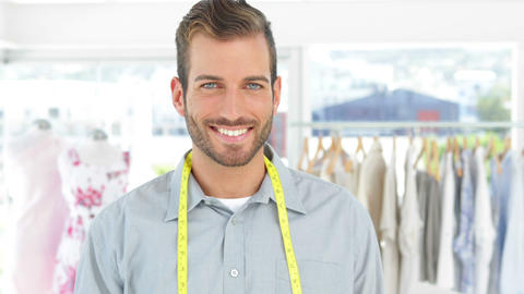 Handsome fashion designer holding a scissors smiling at... Stock Video Footage