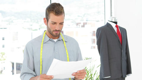 Handsome fashion designer looking at sketches and suit on... Stock Video Footage