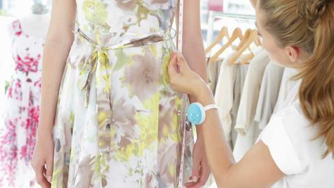 Pretty fashion designer measuring floral dress on a model Stock Video Footage