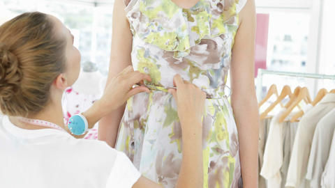 Pretty fashion designer tying belt of floral dress on a... Stock Video Footage