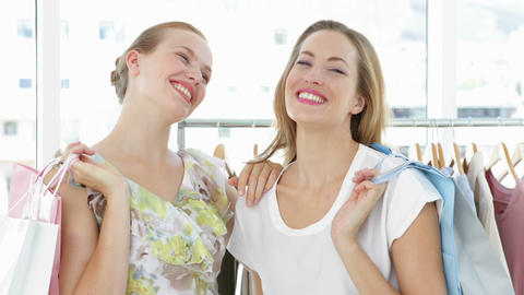 Two friends holding shopping bags smiling at camera Stock Video Footage