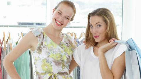 Two pretty friends holding shopping bags smiling at camera Stock Video Footage