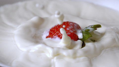 Strawberry falling in glass of milk Stock Video Footage