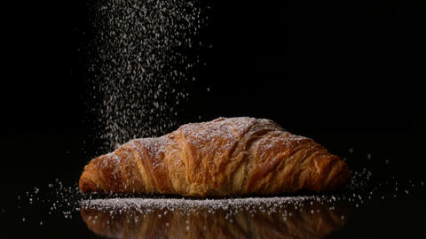 Powdered sugar sprinkling onto a croissant Stock Video Footage