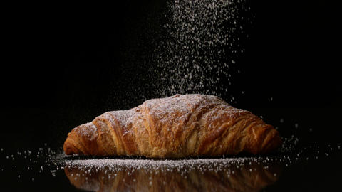 Powdered sugar sprinkling onto a croissant Live Action
