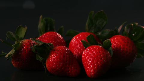 Water drops on strawberries on black surface Stock Video Footage