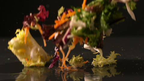 Salad falling onto black surface Stock Video Footage