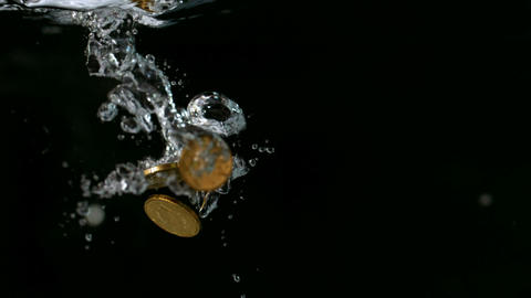 Euro coins falling into water Stock Video Footage