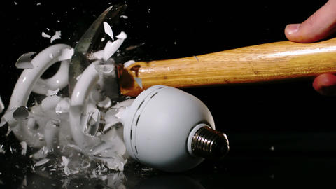 Hammer smashing light bulb on black background Stock Video Footage