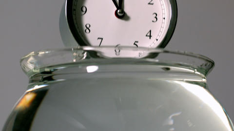 Alarm clock falling into bowl of water Stock Video Footage