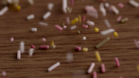 Colourful sprinkles pouring onto surface Stock Video Footage