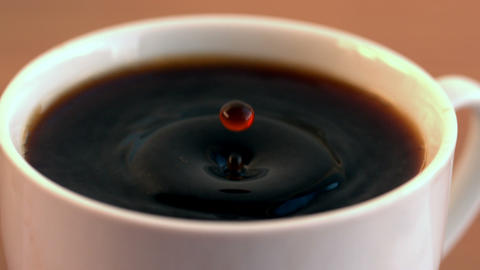 Drop falling into cup of coffee Stock Video Footage
