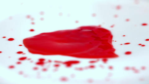Blood dropping onto white surface Footage