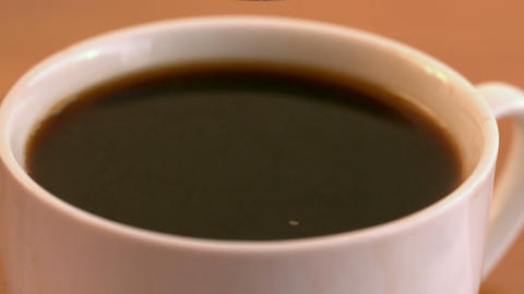 Teaspoon of sugar plunging into coffee cup Stock Video Footage