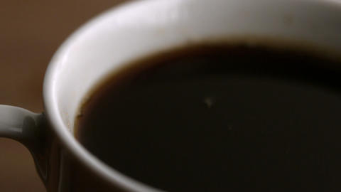 Milk drop falling into coffee cup Stock Video Footage