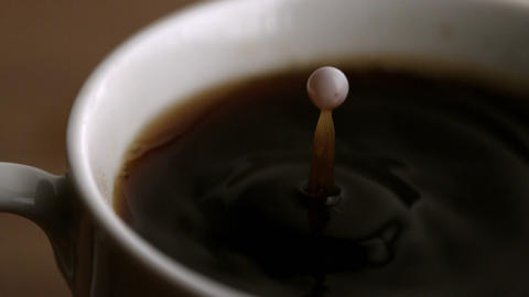 Milk drop falling into coffee cup Footage