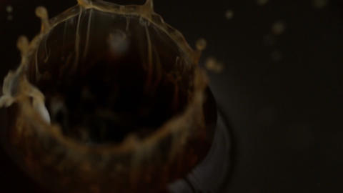 Milk drops falling into coffee cup Stock Video Footage