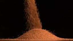 Golden sugar pouring on black background Stock Video Footage