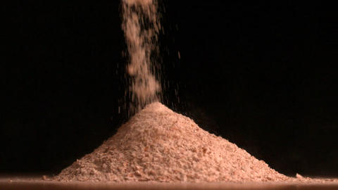 Flour pouring on black background Stock Video Footage