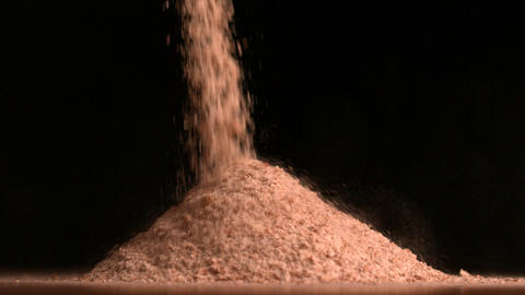 Flour pouring on black background Footage