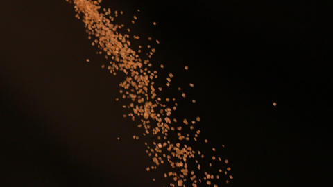 Golden sugar falling against black background Footage