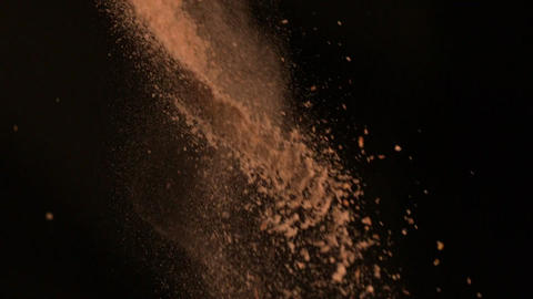 Brown flour falling against black background Stock Video Footage