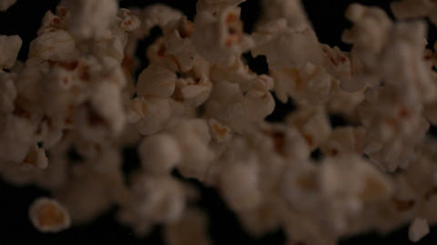 Popcorn bouncing against black background Stock Video Footage