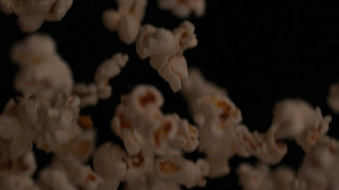 Popcorn bouncing against black background Footage