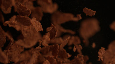 Cereal flakes bouncing against black background Stock Video Footage