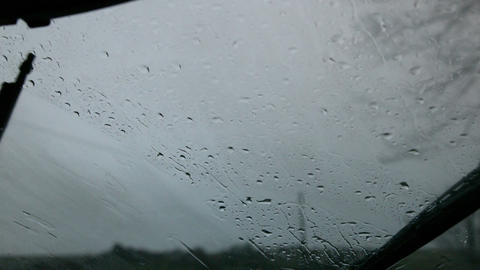Windscreen wiper wiping rain away from car window Footage